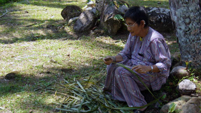 Lady cutting branches to make a broom