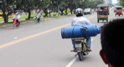 Cambodian biker carries gas bottle