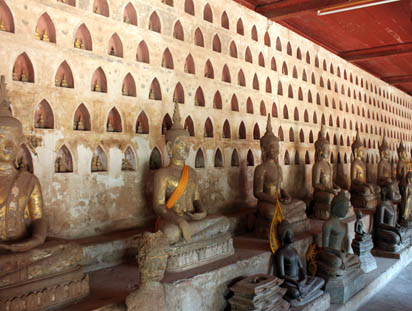 Sitting Buddhas line the temple exterior wall